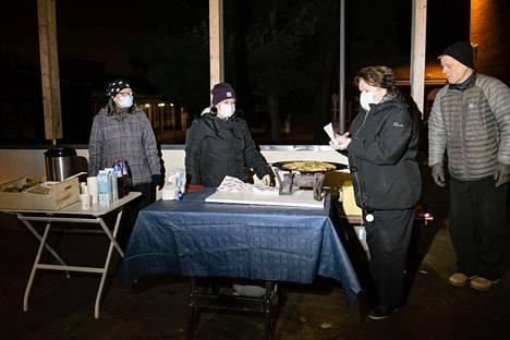 Koulun pihalla pizza lämmitetään kaasukäyttöisellä lämmittimellä. Vas. Asta Haataja, Svetlana Stojcheska, Anneli Virtanen ja Markku Virtanen valmistelevat tarjoiluja.