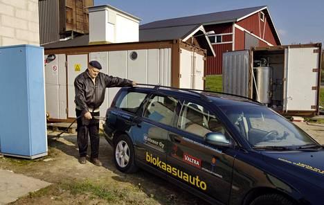 Erkki Kalmari tankkaa navetan takana autoaan omalla biokaasulla. Taustalla ovat tuotantolaitokset. Kuva vuodelta 2005.