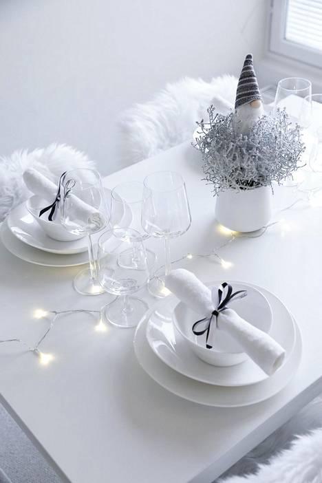 Yksinkertainen kattaus muuttuu juhlavaksi, kun pöydälle asettelee valosarjan ja pienen tontun.