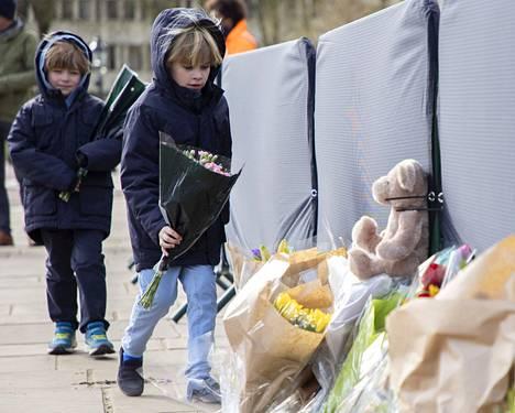 Lapset tuovat Buckinghamin palatsin edustalle kukkia ja nalleja kuolleen prinssin muistoksi.