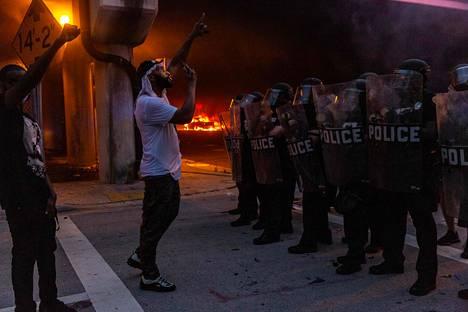 Mielenosoittaja kohtasi poliisit palavan poliisiauton edessä Miamissa lauantaina.