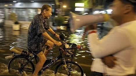 Mies polkee pyörällä Bangkokin Chinatownissa. Kymmenettuhannet kaupunkilaiset jättivät Bangkokin viikonlopun alla.