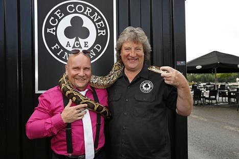 Pytonkäärmeen omistaja Timo Paasikunnas ja Suomen moottoripyörämuseon Riku Routo poseerasivat Minea-pythonin kanssa ennen kuin käärme hyökkäsi morsiamen kimppuun.