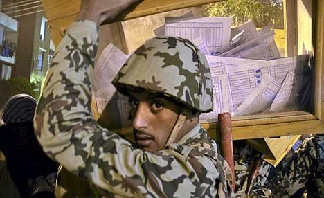 Egyptiläissotilas kantoi vaaliuurnaa äänestyksen päätyttyä Luxorissa tiistaina.