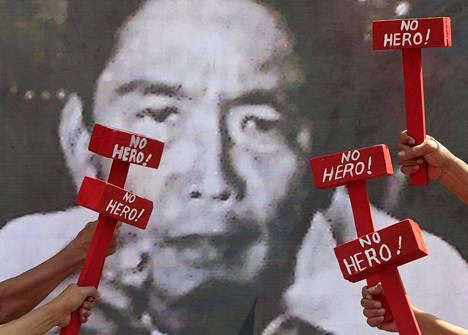 """""""Ei sankari"""", luki mielenosoittajien mukanaan kantamissa leikkivasaroissa. Taustalla Ferdinand Marcosin kuva."""