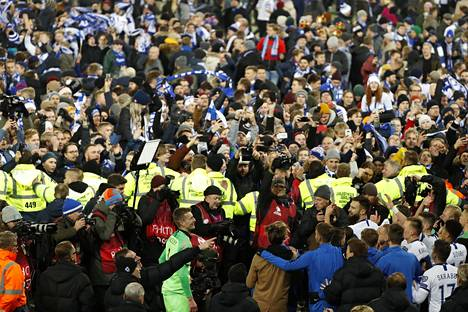 Järjestyksenvalvojat asettuivat lopulta riviin pelaajien ja kentälle olleiden fanien väliin.