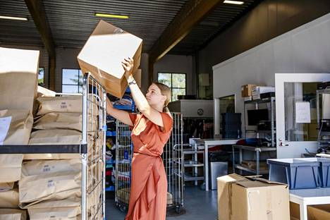 Siri Kurkinen on pakannut asiakkaan tilaamat vaatteet valmiiksi postitusta varten.