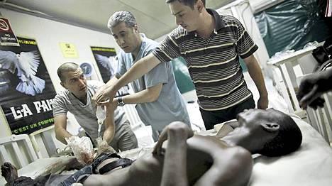 Jordanialaiset lääkärit hoitavat harhaluodin haavoittamaa nuorukaista Abidjanissa.