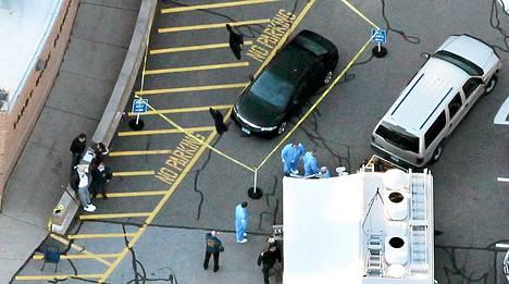 Poliisi ympäröi teipillä autoa Sandy Hookin ala-asteen pihassa.
