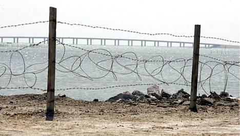 Piikkilanka-aitaa ja taustalla 27 kilometriä pitkä silta, joka yhdistää Bahrainin Saudi-Arabiaan.