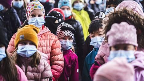 Ilpoisten koulun oppilaita kasvomaskeineen välitunnilla Turussa huhtikuussa. Kaikki koulun oppilaat käyttävät kasvomaskia koronapandemian aikana.