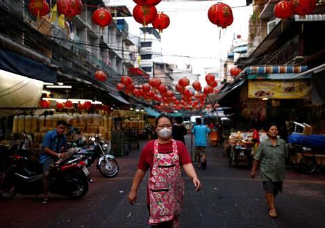 Hengitysuojaimella varustettu nainen kuvattiin Bangkokin kiinalaisessa kaupunginosassa sunnuntaina.