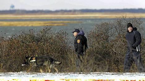Poliisit tutkivat rantakaistaletta uusien ruumiiden pelossa 14. joulukuuta 2010.