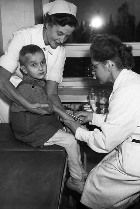 Lääkäri antaa pistoksen tuberkuloosia sairastavalle pojalle.