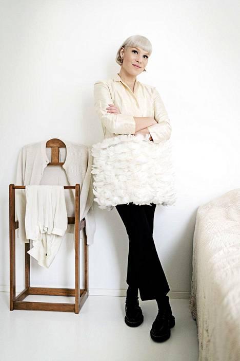 """Suunnittelemansa höyhenjakun Anni yhdistää esimerkiksi mustiin silkkihousuihin. Hän pyrkii usein tekemään mallikappaleet koossa 36–38, """"jotta niitä voi oikeasti käyttää""""."""