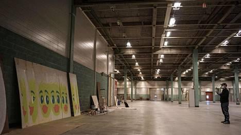 Ossi Pirkkonen maalaa vanerille taideteosta, joka on tarkoitus kiinnittää vanhan teollisuusalueen aitaan Espoon Kerassa.
