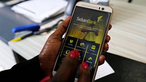Asiakas käyttää mobiilimaksusovellusta Nairobissa, Keniassa.