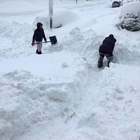 Ihmiset kaivoivat tietä talolta maantielle Eriessä Tapaninpäivänä.