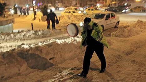 Liikennepoliisi yritti suojautua purevalta tuulelta torstaina Bukarestissa.