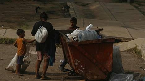Köyhä äiti ja kaksi lasta keräämässä roskia San Franciscon alueella Venezuelassa.