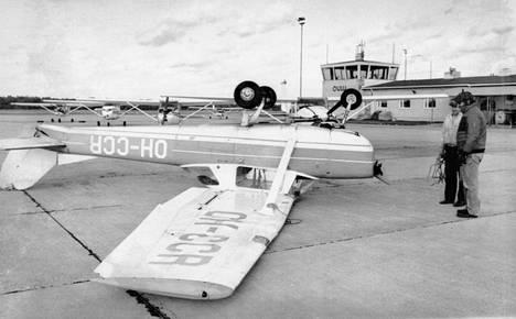 Lentokonemekaanikot Oulunsalossa miettivät, miten kääntää myrskytuulen pyöräyttämä lentokone.