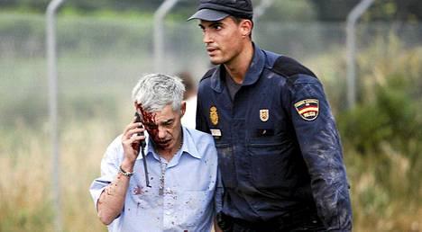 Poliisi auttoi junan kuskiksi väitettyä Francisco José Garzónia (vas.) heti turman jälkeen.