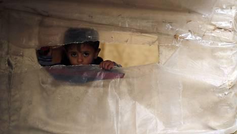 Palestiinalaispoika kurkki Gazassa Reutersin kuvaajaa perheen muovista ja muusta epämääräisestä materiaalista kyhätyn tilapäiskodin ikkunasta. Perheen koti tuhoutui Gazan viime kesän 50-päiväisessä sodassa.