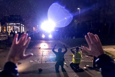 """""""Älä ammu"""", protestoijat huusivat polvistuessaan poliisin eteen poliisiasemalla."""