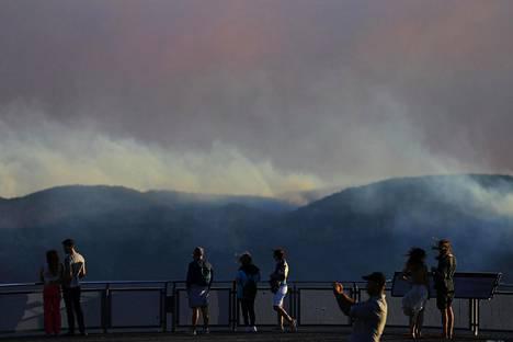 Ihmiset kerääntyivät katselemaan savupilveä.