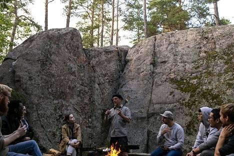 Rami Heinäluoto (kesk.) johdatti vieraat nuotiopaikalle kallion kylkeen.