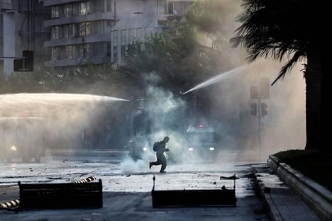 Mielenosoittaja väisteli poliisin vesitykkejä ja kyynelkaasua.