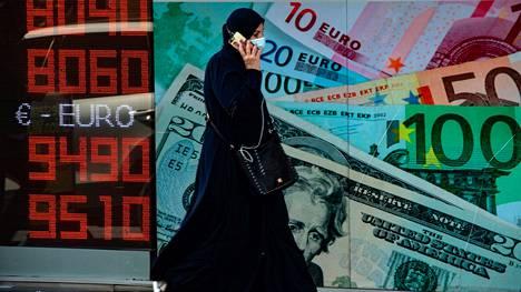 Nainen käveli valuuttakursseja näyttävän valotaulun ohitse Istanbulissa Turkissa 26. lokakuuta.