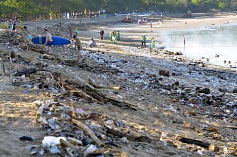 Turistit kävelevät roskavuorien keskellä Kuta-beachillä. Merivirtojen ja aaltojen myötä rantaan ajautuu roskaa merellä kelluvista jäteryppäistä.