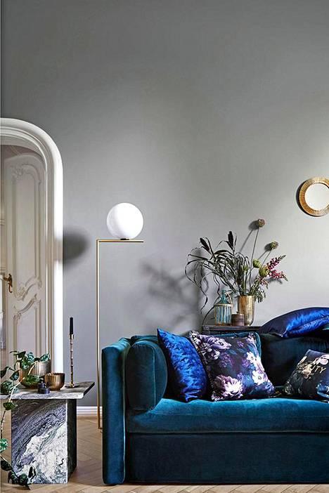 Sametti voi olla hyvinkin näyttävästi esillä olohuoneessa esimerkiksi syvän safiirinsinisen sohvan muodossa. Klassista sohvaa tasapainottavat moderni valaisin sekä minimalistinen sohvapöytä. H&M.