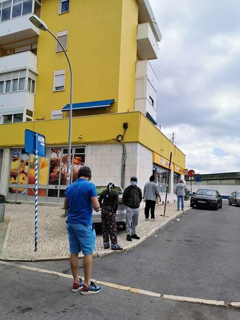Lähikauppaan jonotetaan Lissabonissa ulkona turvavälin kera.