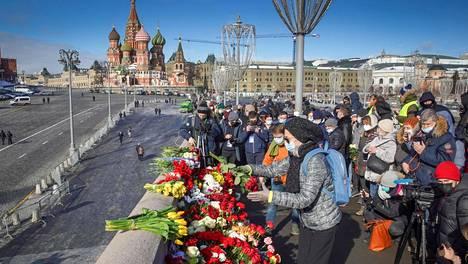 Nainen laskee kukkia Boris Nemtsovin murhapaikalle Moskovan keskustassa 27. helmikuuta 2021.