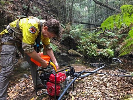 Palomies lisää polttoainetta vesipumpun säiliöön.