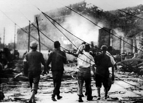 Elokuun 6. päivänä 1945 otettu valokuva ilmasuojelumiehistä, jotka kantavat uhria Hiroshimassa.