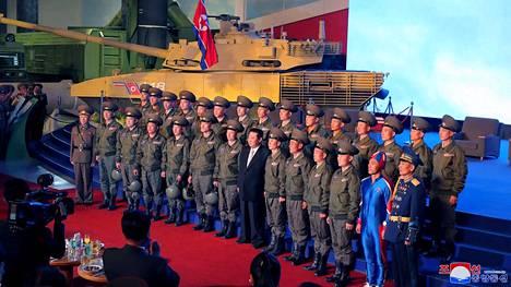 Siniseen kokovartalopukuun pukeutunut mies poseeraa kuvassa Pohjois-Korean johtajan kanssa.