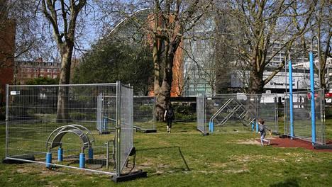 Lontoolaislapset leikkivät huhtikuun alkupuolella leikkipuistossa, jonka välineiden käyttö oli estetty aidoilla.
