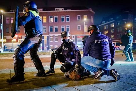Poliisit pidättivät miestä mielenosoitusten yhteydessä maanantaina.