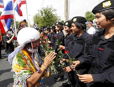 Mielenosoittajat jakoivat poliiseille kukkia.