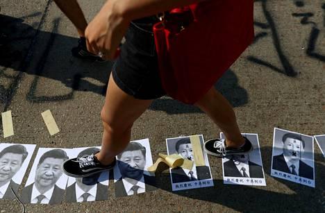 Presidentti Xi Jinpingin kuvat saivat kyytiä mielenosoittaja jalkojen alla.