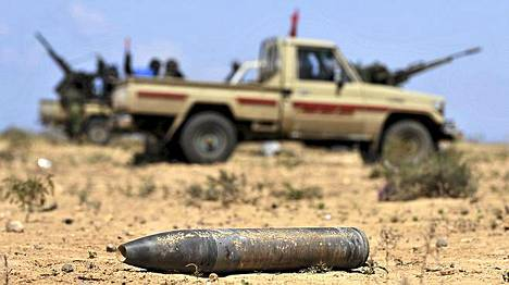 Libyan kapinalliset ohittavat räjähtämättä jääneen tankin ammuksen.