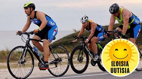 Chris Nikic (etummaisena) kuvattiin triathlonin pyöräilyosuudella viime lauantaina Floridan Panama Cityssä. Perässä oikealla ajaa hänen valmentajansa Dan Grieb.