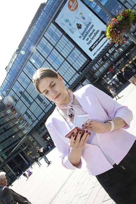 Laura Kemppainen käyttää puhelinta Kampin Narikkatorilla.