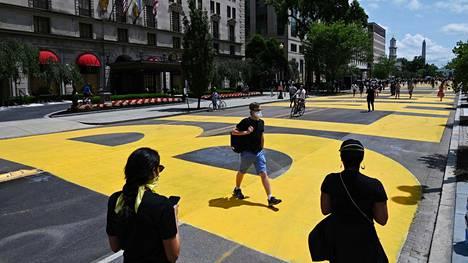 Vapaaehtoiset olivat mukana maalaamassa kirkuvankeltaista viestiä kadun pintaan.