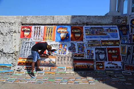 Katutaiteilija kauppaa matkamuistoteoksia Kalk Bayn kalastajakaupungissa.