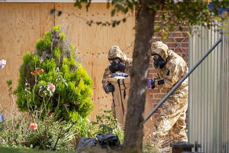 Britannian asevoimien edustajat tutkivat Sergei Skripalin asunnon edustaa. Novitshok-hermomyrkyn vuoksi etsivillä on yllään suoja-asut.