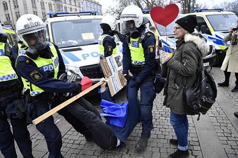 Poliisi kantaa mielenosoittajaa, joka osoitti mieltä hallituksen koronarajoituksia vastaan Malmössä maaliskuussa.